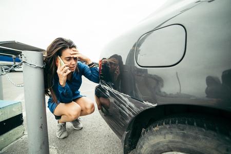 kick around: sad woman standing near car with scratch