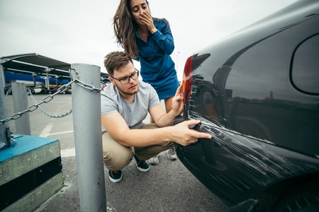 sad man looking on car scratch, woman stand behind him