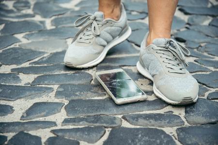 gebarsten smartphone-scherm in de buurt van benen