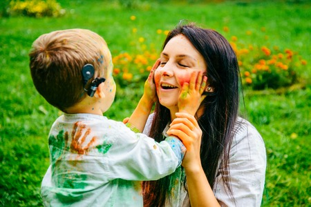 Happy mother and son playing with holi paints