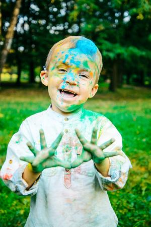 happy little kid all in holi paints