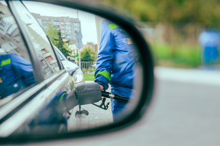 oil and gas industry: reflection in car mirror of the man fuel the car Stock Photo