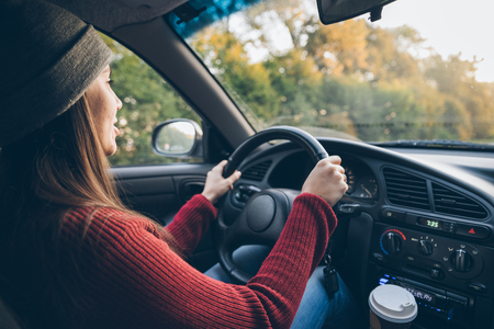 Happy young woman driving her car with coffee Stock Photo