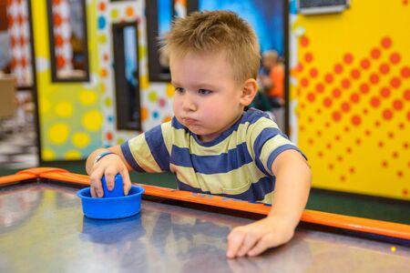 little kid plays in air hokey