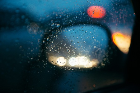 Raindrops on the car rearview mirror.