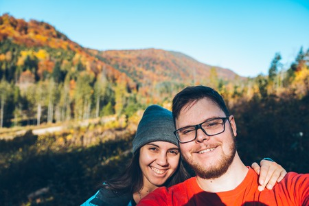 Couple taking self portrait in mountains with smartphone