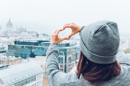 woman shows heart with hands with beautiful view of old european city on background