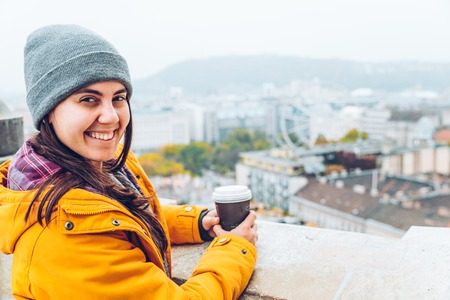 woman with cup of coffe looking at european city