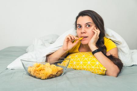 여자가 나쁜 시계 영화에 누워서 snak를 먹는다. 스톡 콘텐츠