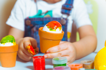 mother with kid painting eggs for easter Stock Photo