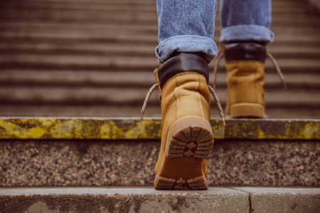 womans boots close up climb up by old stairs Stock Photo
