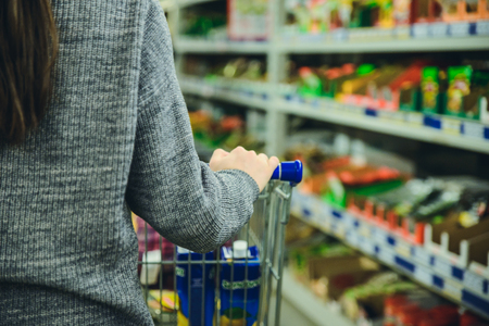 woman push trolley by supermarket buy products