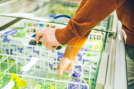 man get frozen food from fridge in store. shopping concept
