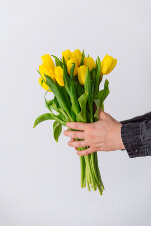 man's hand hold bouquet of yellow tulip. love symbol