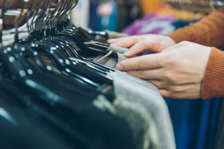 man hands close up looking for clothes in store. shopping concept Stock Photo