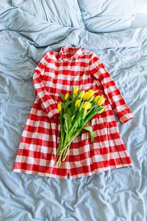 bouquet of yellow tulips on red woman checkered dress. romantic spring concept Stock Photo