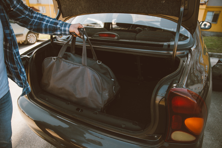 man put bags to car trunk. car travel concept Foto de archivo