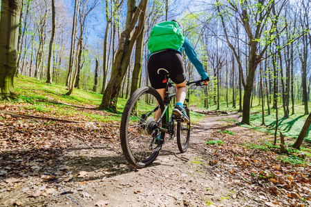 young woman ride bicycle in forest by trail