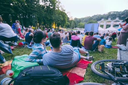 people watching movie in open air cinema in city park