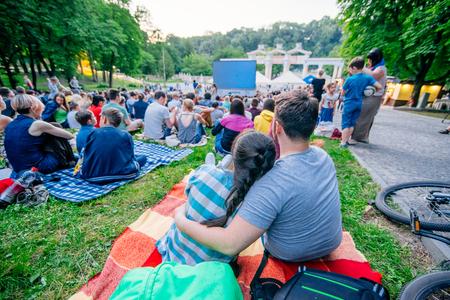 persone che guardano film nel cinema all'aperto nel parco cittadino