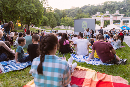 LVIV, UKRAINE - JUNE 1, 2018: people sitting on grass in city park watching movie in open air cinema
