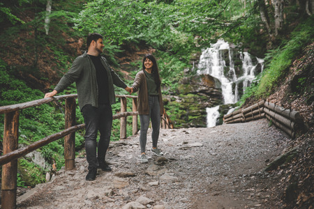 couple walk holding hands. waterfall on background.