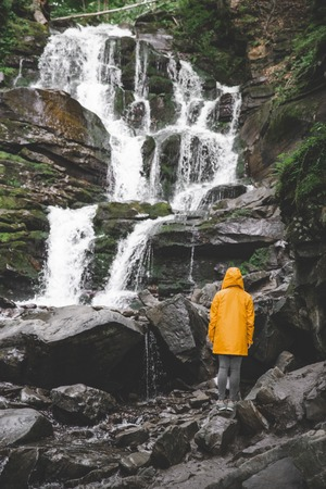 woman standing in yellow raincoat and looking at waterfall