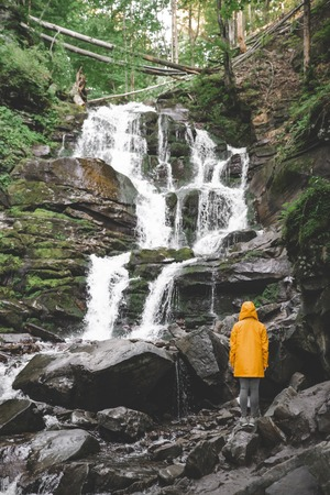 woman standing in yellow raincoat and looking at waterfall. hiking concept Stock Photo - 107155385