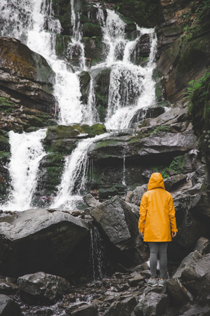 woman standing in yellow raincoat and looking at waterfall. hiking concept Stock Photo