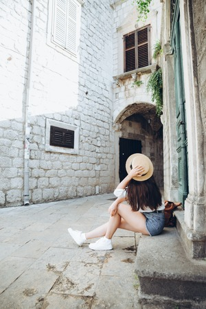 woman sitting on stairs outside at summer day. copy space