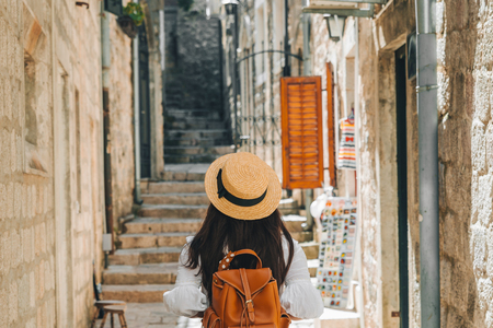 woman walking by kotor city in sunny day. view from behind