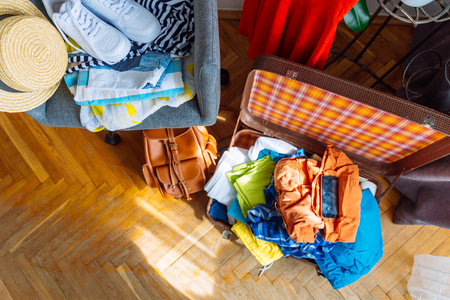 overloaded valise with clothes. prepared garment on chair. travel concept Stock Photo