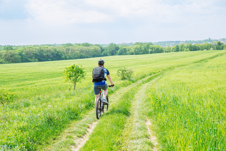 man riding bicycle by trail in green barley field. copy space Stock Photo