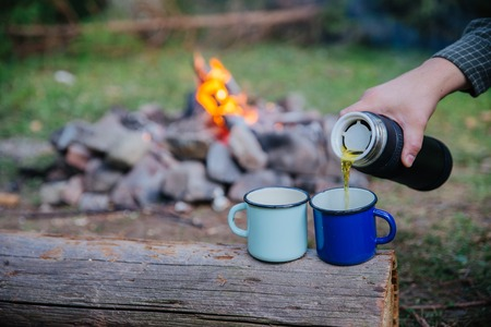 hand pour tea into metal cups. camp fire on background. hiking concept