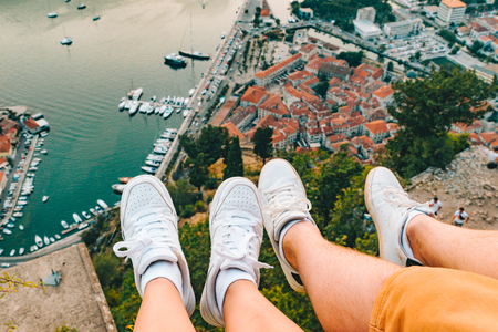 couple legs at hill with beautiful view of kotor city on background. summer vacation
