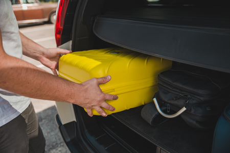hands load bags in car trunk. car travel concept