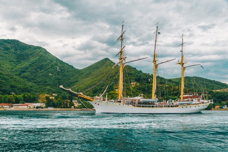 sail ship at sea with beautiful view of mountains on background. summer time