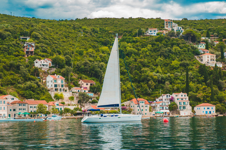 white yacht at sea with mountains and small town on background. summer vacation