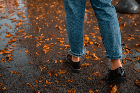 woman walking by wet streets after rain. yellow leaves on ground.