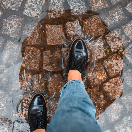 first person point of view woman step into puddle in black shoes