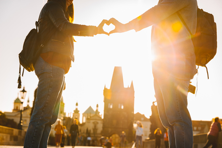 lovers make heart symbol at charles bridge in prague. lovers travel concept