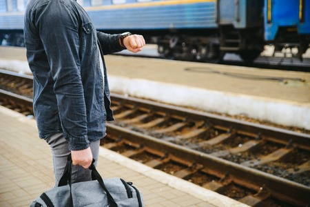 travel concept. man hold bag close up on railway station
