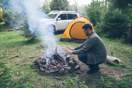 man build fire in forest, car with yellow tent on background. camping Stock Photo