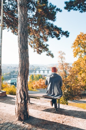 man sitting on bench with beautiful view of autumn prague. lonely minds