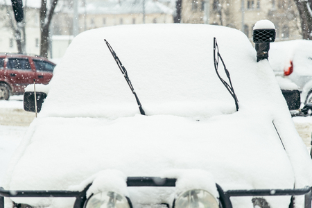 car covered with snow on outdoors parking in winter day. lifestyle