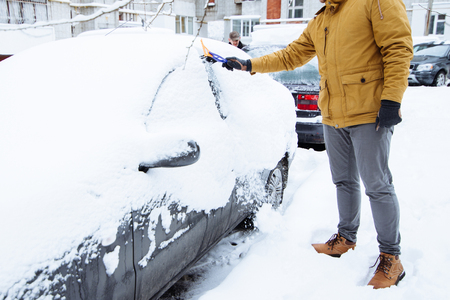 man cleaning car after snowstorm. streets covered snow Stock Photo