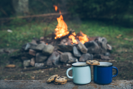 two metal cups with tea and cookies. fire on background. union with nature