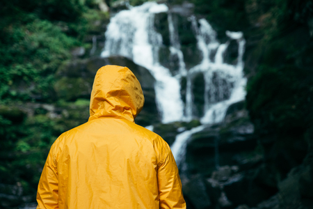 man standing in yellow raincoat and looking at waterfall. hiking concept Stock Photo