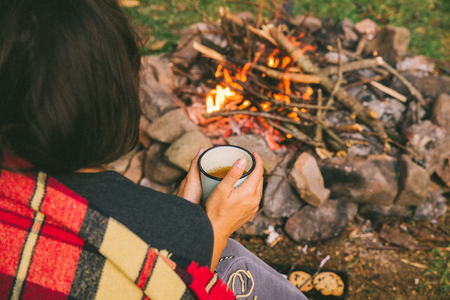 woman sitting near fire with cup of tea. hiking concept