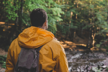 man stand in the middle of forest in yellow raincoat. hiking concept